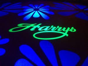 Gobos med Harrys logga och blommor på nattklubbsgolv.