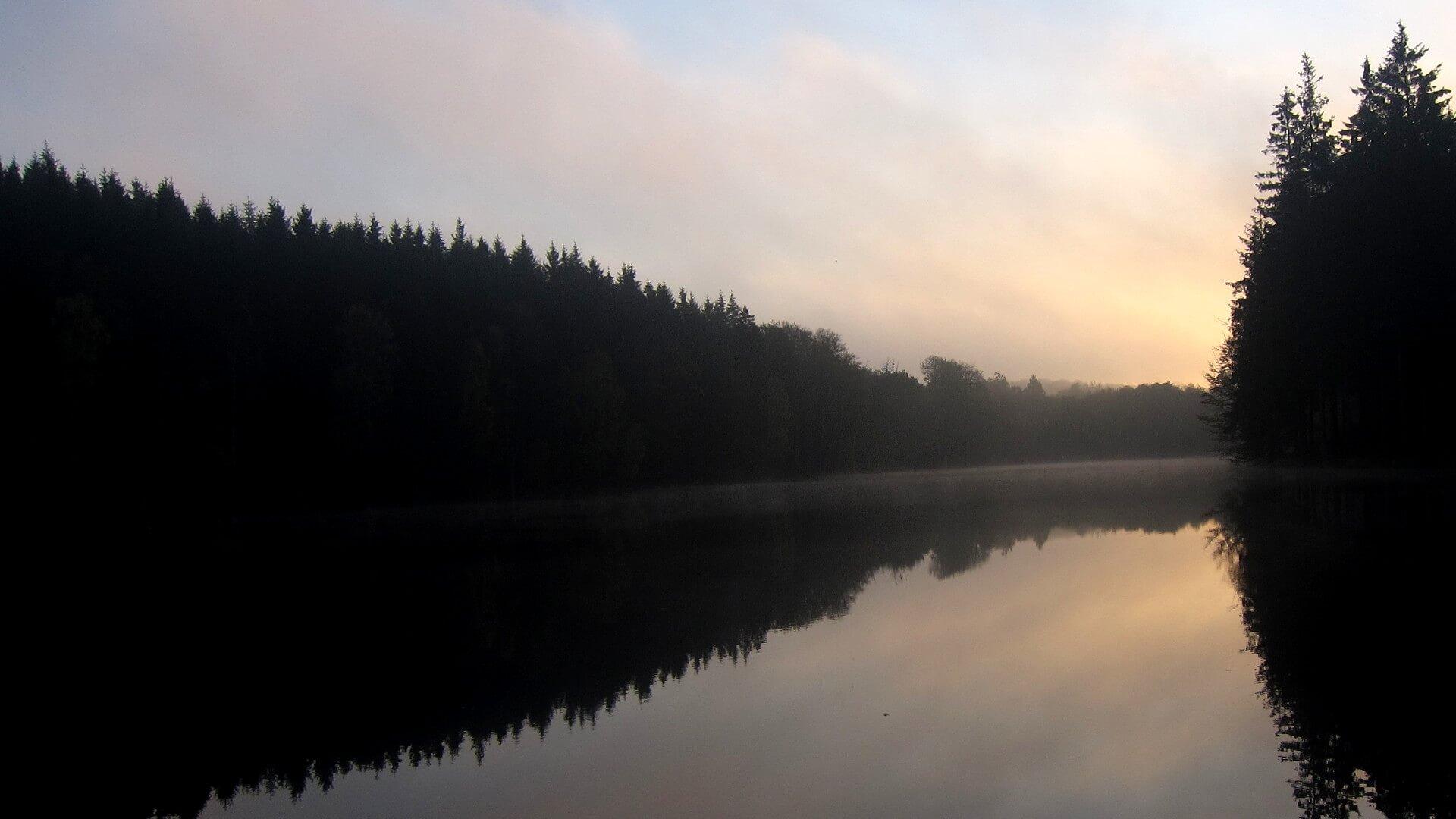 Soluppgång över en insjö på Söderåsen